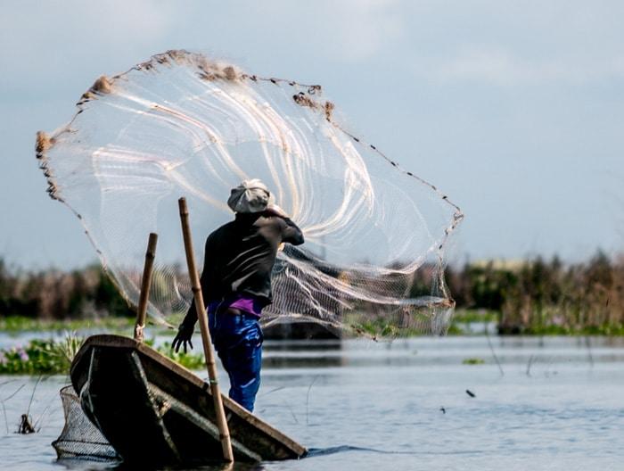 Photo sur lac au Bénin, un pécheur jête son filet
